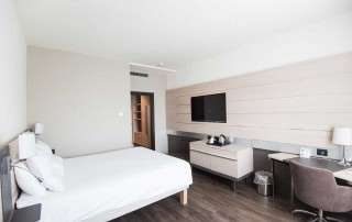 Smart tech, modern hotel room with white walls, white bed, and light colored furniture. Smart TV on the wall.