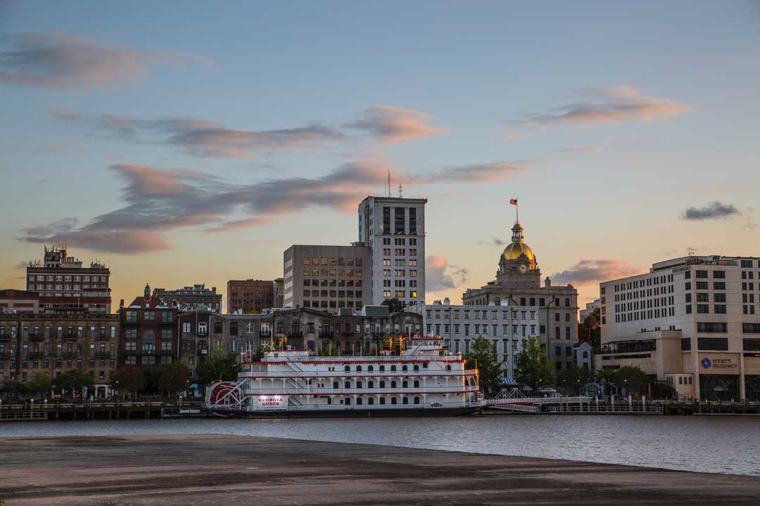 The skyline of the city of Savannah Georgia with water in front and a white steam boat.