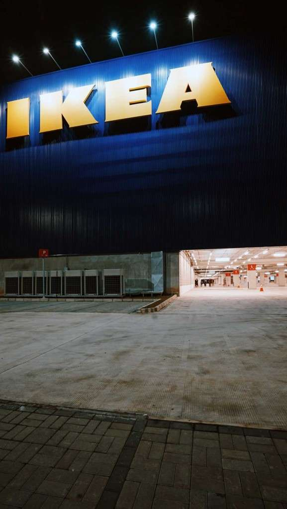 An IKEA late at night with the IKEA logo lit up and a dark parking lot area.